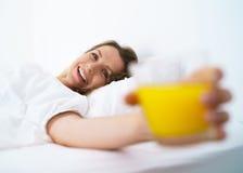 Ragazza sveglia che dorme a letto svegliando allungamento, sorridere e drin Fotografie Stock Libere da Diritti