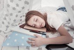 Ragazza sveglia che dorme sui suoi taccuini Fotografia Stock Libera da Diritti