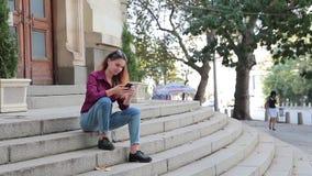 Ragazza sveglia che esamina il suo telefono che si siede sui punti all'aperto archivi video