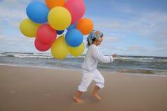 Ragazza sveglia che gioca con gli aerostati sulla spiaggia Fotografie Stock Libere da Diritti