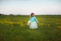 Ragazza sveglia che gioca in un campo Fotografie Stock