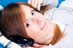 Ragazza sveglia che gode della musica. Esaminando macchina fotografica Fotografia Stock