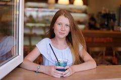 Ragazza sveglia che guarda dalla finestra e dalla limonata blu bevente Fotografia Stock