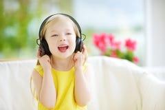 Ragazza sveglia che indossa le cuffie senza fili enormi Bambino grazioso che ascolta la musica Scolara divertendosi ascoltare le  Fotografie Stock Libere da Diritti