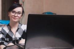 Ragazza sveglia che lavora al computer portatile a casa, Immagini Stock