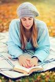 Ragazza sveglia che legge un libro in parco Fotografie Stock Libere da Diritti