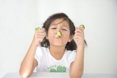 Ragazza sveglia che mangia i broccoli bolliti Fotografia Stock