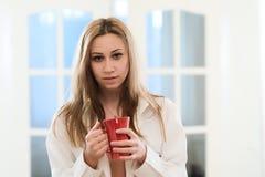 Ragazza sveglia che mangia un caffè di mattina fotografia stock libera da diritti