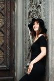 Ragazza sveglia che modella aspetto che posa contro il contesto di belle porte enormi in vestito e cappello neri immagine stock libera da diritti