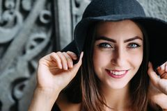 Ragazza sveglia che modella aspetto che posa contro il contesto di belle porte enormi in vestito e cappello neri immagini stock