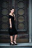 Ragazza sveglia che modella aspetto che posa contro il contesto di belle porte enormi in vestito e cappello neri fotografia stock