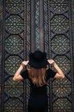 Ragazza sveglia che modella aspetto che posa contro il contesto di belle porte enormi in vestito e cappello neri immagini stock libere da diritti