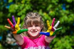 Ragazza sveglia che mostra le sue mani dipinte nei colori luminosi Mani verniciate bianche ambulanti Immagini Stock Libere da Diritti