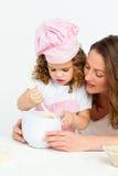 Ragazza sveglia che prepara una torta con la sua madre Immagine Stock