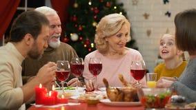 Ragazza sveglia che racconta storia divertente agli adulti alla cena di festa, celebrazione di famiglia video d archivio
