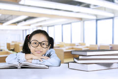 Ragazza sveglia che si siede con i libri in aula Immagine Stock