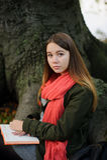 Ragazza sveglia che si siede contro il contesto di vecchio albero enorme Fotografia Stock Libera da Diritti