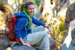 Ragazza sveglia che si siede sul gambo caduto dell'albero in foresta selvaggia Fotografie Stock Libere da Diritti