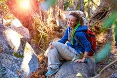 Ragazza sveglia che si siede sul gambo caduto dell'albero in foresta selvaggia Immagini Stock