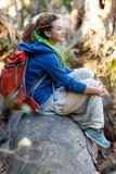 Ragazza sveglia che si siede sulla foresta del gambo dell'albero che gode del sole caldo Fotografie Stock Libere da Diritti