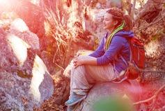 Ragazza sveglia che si siede sulla foresta del gambo dell'albero che gode del sole caldo Fotografia Stock Libera da Diritti