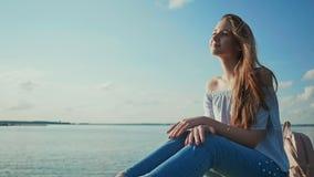 Ragazza sveglia che si siede sulla spiaggia che guarda il tramonto e che posa sorridere archivi video
