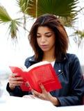 Ragazza sveglia che si siede in un caffè sul lungomare e leggente un libro sulle finanze Immagini Stock Libere da Diritti