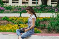Ragazza sveglia che si siede vicino ai letti di fiore con i fiori e che esamina computer portatile Fotografia Stock Libera da Diritti