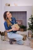 Ragazza sveglia che si siede vicino all'albero di Natale con un regalo Immagine Stock Libera da Diritti