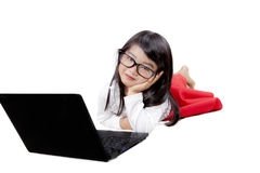Ragazza sveglia che si trova con un computer portatile Fotografie Stock