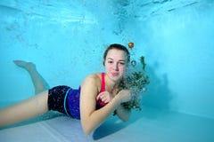 Ragazza sveglia che si trova underwater al fondo dello stagno nelle bolle di aria, esaminante macchina fotografica e sorridere Fotografia Stock Libera da Diritti