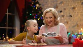 Ragazza sveglia che soffia alla polvere dello zucchero sui muffin, nonna che sorride, tempo di natale della famiglia video d archivio