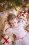 Ragazza sveglia che sogna sotto l'albero di Natale con i regali immagine stock libera da diritti