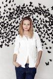 Ragazza sveglia che sta su un fondo fantastico con i lotti delle farfalle Immagine Stock