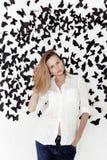 Ragazza sveglia che sta su un fondo fantastico con i lotti delle farfalle Fotografia Stock