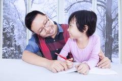 Ragazza sveglia che studia con il suo papà a casa Immagine Stock Libera da Diritti