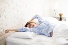 Ragazza sveglia che sveglia sul suo letto Fotografia Stock Libera da Diritti