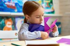 Ragazza sveglia che taglia cuore di carta nella classe del mestiere immagine stock