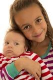 Ragazza sveglia che tiene sua sorella del bambino in pigiami a strisce Fotografia Stock Libera da Diritti