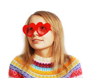 Ragazza sveglia con i vetri heart-shaped rossi su bianco Fotografia Stock