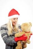 Ragazza sveglia con il cappello di Santa Claus, abbracciante un orsacchiotto Fotografia Stock Libera da Diritti