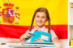 Ragazza sveglia con il libro e la bandiera spagnola dietro Fotografia Stock Libera da Diritti