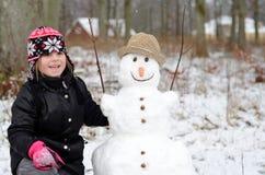 Ragazza sveglia con il pupazzo di neve Fotografia Stock