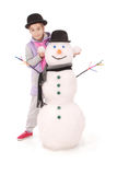 Ragazza sveglia con il pupazzo di neve con la sciarpa ed il cappello Fotografie Stock
