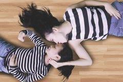 Ragazza sveglia con la mamma che si trova nel pavimento Fotografia Stock