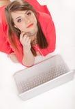 Ragazza sveglia con le cuffie e la menzogne del computer portatile isolata Fotografia Stock
