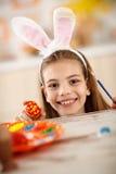 Ragazza sveglia con le orecchie dipinte del coniglietto e dell'uovo fotografia stock