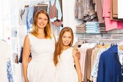 Ragazza sveglia con sua madre in attrezzatura bianca al negozio immagine stock libera da diritti