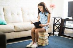 Ragazza sveglia con un libro che si siede su un mucchio dei libri Fotografia Stock