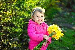 Ragazza sveglia con un mazzo dei narcisi gialli nel giardino di primavera Fotografia Stock
